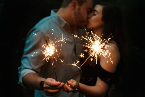 Couple holding sparklers and kissing.