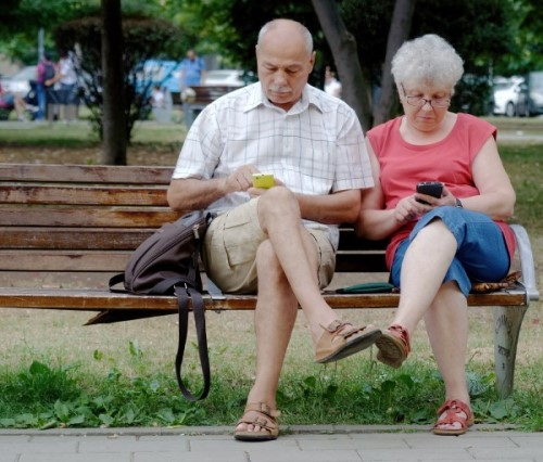 A couple, each on their own smartphone.