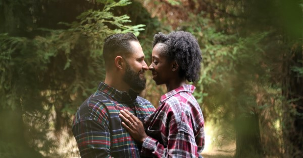 Couple gazing at each other in a forest clearing.